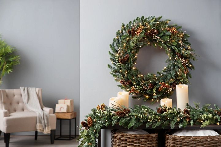 Decorated artificial wreath and garland with lights on a console table
