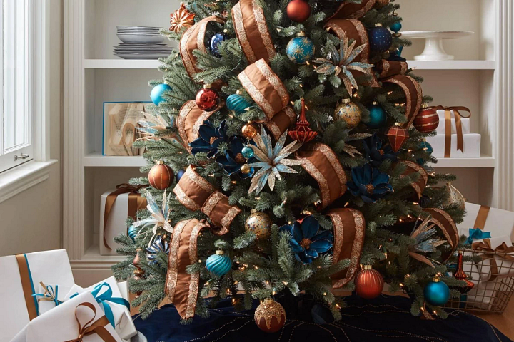 Christmas decorating with assorted blue, gold, and orange ornaments on a realistic tree