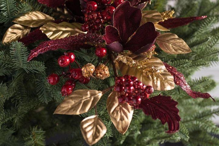 Weihnachtszweige mit Blumen in bordeauxrot und Gold an einem Weihnachtsbaum
