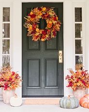 Fall-themed floral wreath and potted foliage on front door