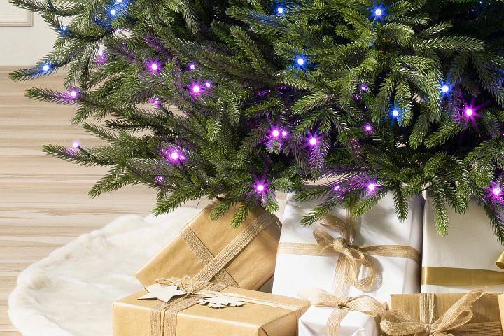 Close-up shot of a Christmas tree with blue and violet lights