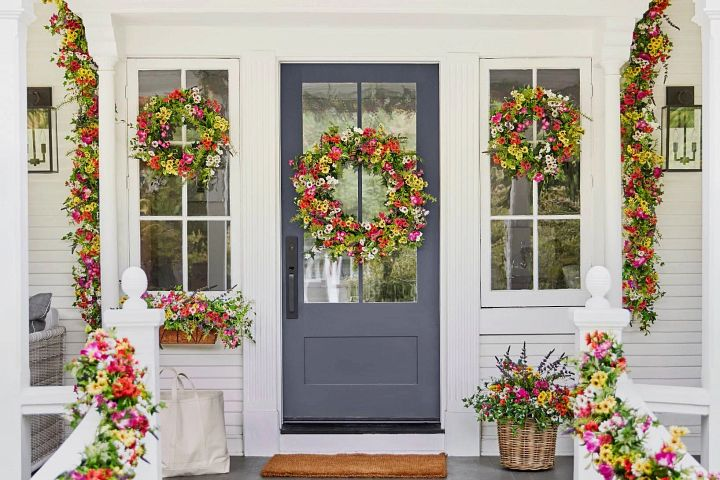 Alt text: Colorful artificial wreaths, garlands, and potted foliage on a porch