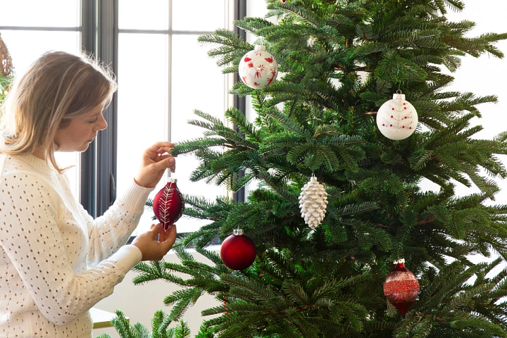 Woman placing red and white ornaments on a Balsam Hill artificial Christmas tree